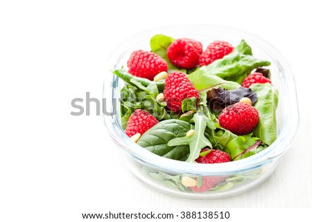 Green  salad with arugula and berries and pine nuts on white  - stock photo
