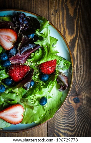 Green salad with berries on wooden background - stock photo
