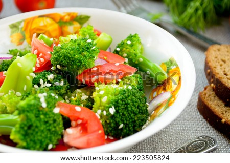 Green salad with broccoli, tomato and sesame seed - stock photo