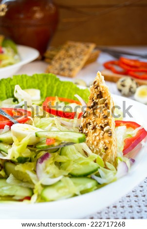 Green salad with cabbage, paprika, cucumber, quail eggs and cereal crackers