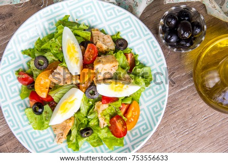 Green salad with chicken, lettuce, egg, olives, tomatoes, healthy lunch, tatsy dish