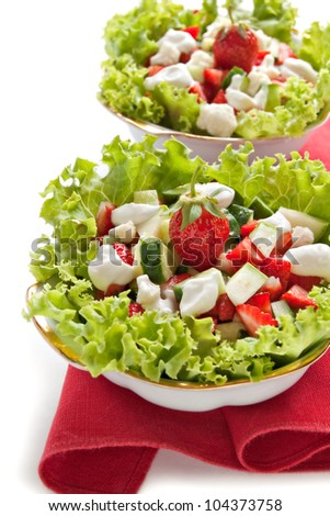 Green salad with cucumber, zucchini and strawberries on a white background