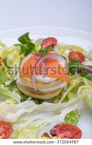 green salad with eggs in the shape of a heart, salmon, cherry tomatoes. a symbol of Valentine's Day. color image