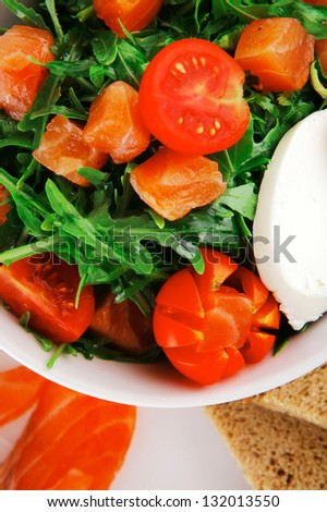 green salad with smoked salmon and bread in white bowl