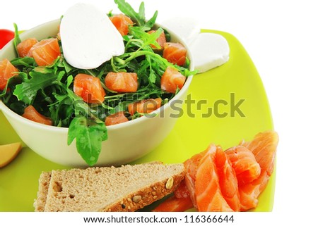 green salad with smoked salmon in bowl on plate