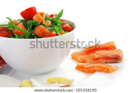 green salad with smoked salmon in white bowl on plate