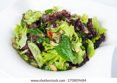 Green salad with spinach,pepper,sweet peas and pumpkin seeds on white background