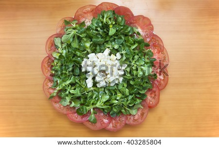 Green salad with tomato, corn salad and cheese - stock photo