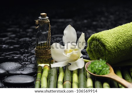 Green salt in spoon with massage oil and thin bamboo with towel grove on mat