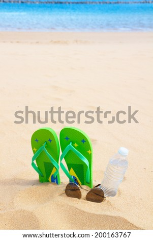 green  sandals  on sandy beach with bottle of clear water and glasses