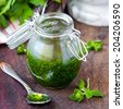 Green sauce marinade from herbs oregano, parsley, oil, traditional chimichuri in glass jar - stock photo