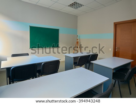 Green school board and tables in the classroom