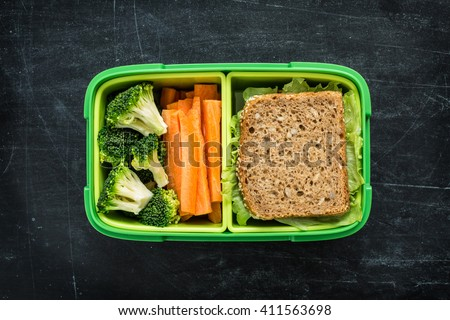 Green school lunch box with sandwich, broccoli and carrot close up on black chalkboard background. Healthy eating habits concept. Flat lay composition (from above, top view). - stock photo