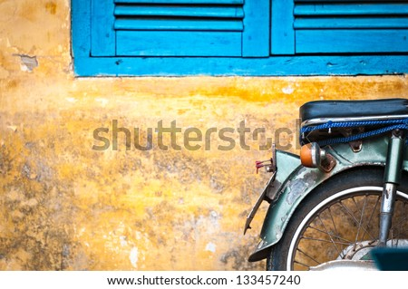 Green scooter against old house. Weathered wall as background. Urban street in Vietnam, Asia. Moped parked at moldy stonewall. Mossy surface of building. Asian lifestyle and popular transport. - stock photo