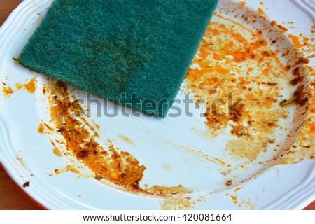 green scrub sponge clean food stain on white plate - stock photo