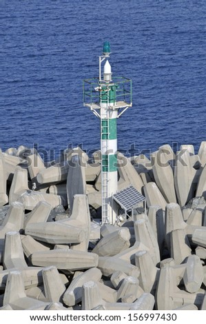 Green sector light tower for shipping navigation built on Dolos concrete blocks on harbour wall sea defences assumed powered by visible solar panels - stock photo