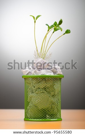Green seedlings growing out of paper - stock photo