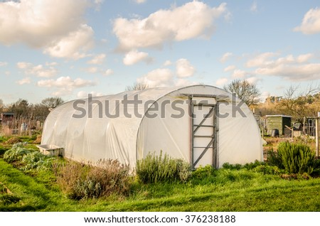 Green self-sufficiency  - Polythene tunnel handmade greenhouse in allotments for growing vegetables. - stock photo