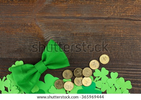 Green Shamrocks clovers on wooden background with green bow and a bunch of gold coins. Background for St. Patrick's Day celebration - stock photo