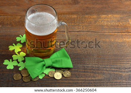 Green Shamrocks clovers on wooden background with lots of gold coins and a large mug of beer with a green bow . Background for St. Patrick's Day celebration - stock photo