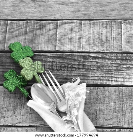 Green Shamrocks with black and white fork and spoon and napkin on rustic wood board background for St. Patricks Day Celebration.  Room or space for copy, text, words. - stock photo