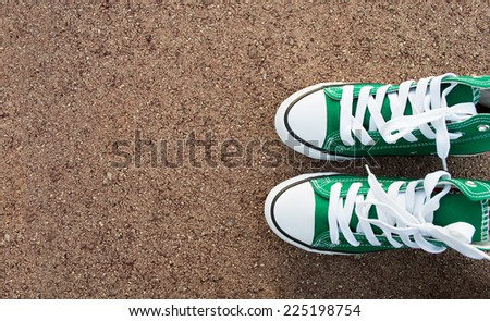green shoes on the asphalt with copy space - stock photo