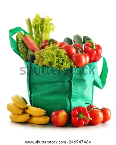 Green shopping bag with variety of fresh organic vegetables isolated on white - stock photo