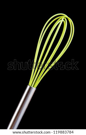 Green silicone cooking beater isolated on black - stock photo