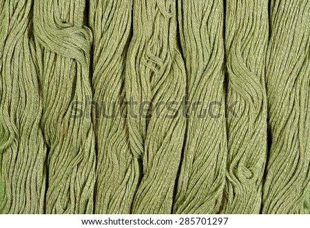 Green skeins of floss as background texture close up