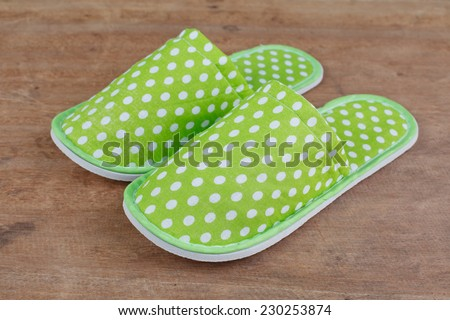 Green slippers on wooden background - stock photo