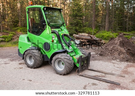 Green small forklift stands on a logging area in forest