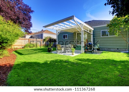 Green small house with porch and backyard with fence. - stock photo