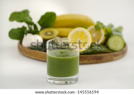 Green smoothie alkaline diet drink with fresh lemon beside a wooden tray with alkaline diet vegetables and fruits: Banana, kiwi, spinach, lemon, cucumber, parsley , silver beat and garlic. - stock photo