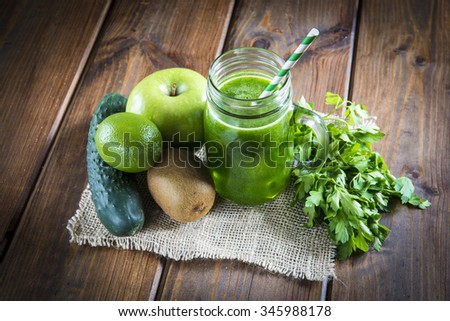 Green smoothie and fresh ingredients on an old wooden background - stock photo