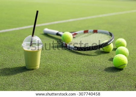 Green smoothie and tennis racket and balls on the court - stock photo