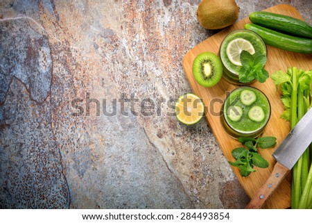 Green smoothie,cucumber,lemon,kiwi and celery on stone background - stock photo