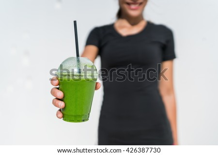 Green smoothie cup waitress woman serving drink at juice bar or cafe. Closeup of plastic take-away disposable container for restaurant business, person holding for healthy eating diet weight loss. - stock photo