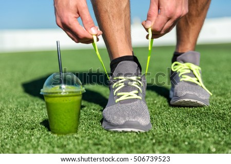 Green smoothie fitness man lacing running shoes, Athlete runner with green vegetable detox juice getting ready for morning run tying running shoe laces on grass. Fitness and healthy lifestyle concept.