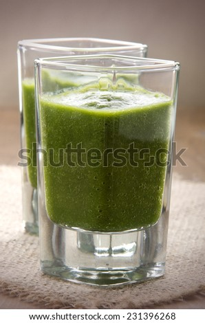 green smoothie made from celery, cabbage and bananas on jute in a shot glass