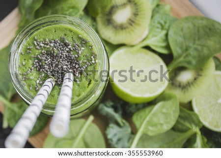 Green smoothie with spinach and kale, kiwi and lime topped with chia seeds. Space for text. - stock photo