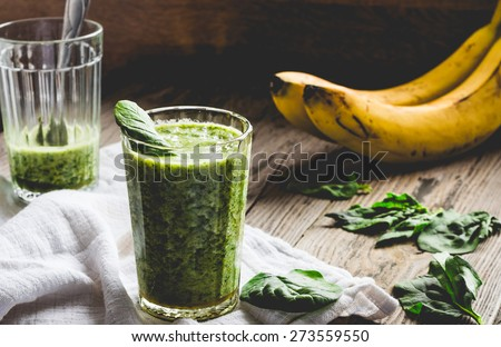green smoothie with spinach leaves, banana with peanut milk in a glass on a gray wooden background - stock photo