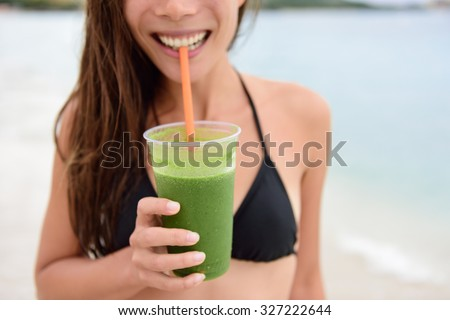 Green smoothie. Woman holding green vegetable detox juice outside in bikini in summer sun on beach. Healthy lifestyle with beautiful mixed race Asian Caucasian female model taking a cleanse diet. - stock photo