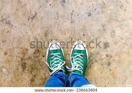 green Sneakers shoes walking on Dirty concrete top view , Canvas shoes walking on concrete - stock photo