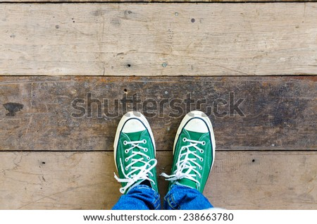 green Sneakers shoes walking on Dirty wooden top view , Canvas shoes walking on wooden  - stock photo