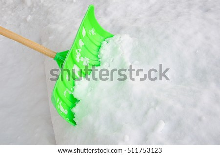 Green snow plastic shovel scooping snow.