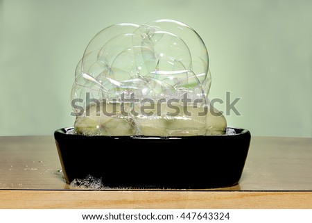 green soap with bubbles on a black soap dish - stock photo