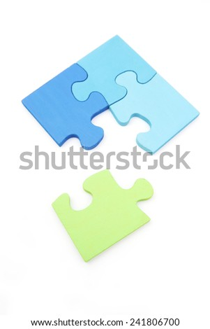 Green solutions - green puzzle piece going into a blue puzzle