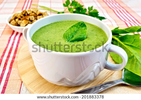 Green soup puree in a bowl with green leaf spinach, spoon on the board, croutons, parsley on a cloth background - stock photo