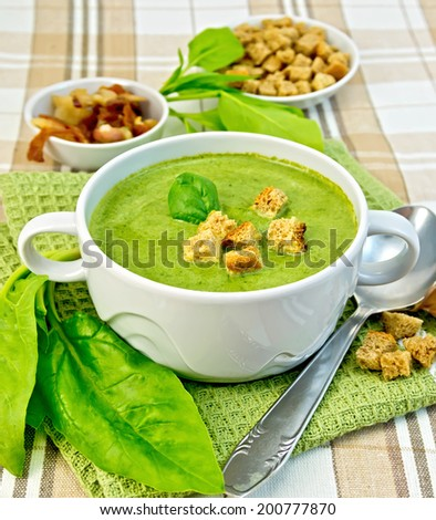 Green soup puree in a white bowl with croutons and spinach leaves, spoon on a napkin and background fabric