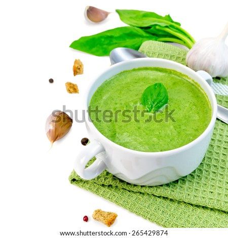 Green soup puree in a white bowl with croutons on a napkin, spinach, spoon, garlic, pepper isolated on white background - stock photo